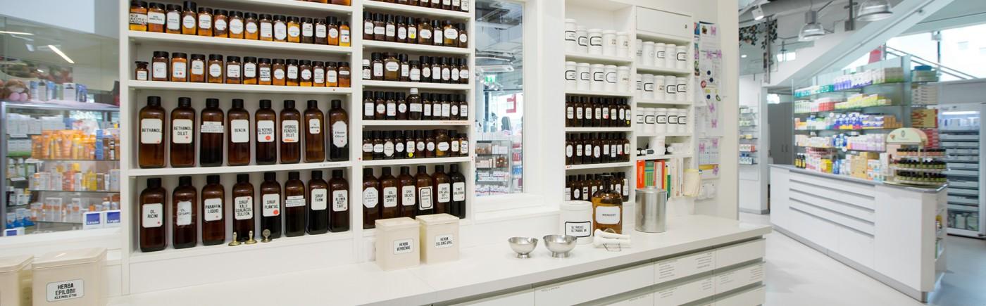 Labor der St georg Apotheke. Regale mit verschiedenen braunen Glas-Standgefäßen und Salbengefäßen. Im Hintergrund sieht man in den Verkaufsraum